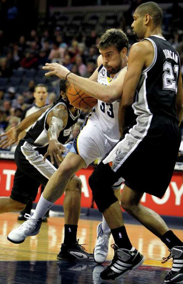 Memphis Grizzlies center Marc Gasol (33), of Spain, drives on San Antonio Spurs forward Tim Duncan (21) during the first half of an NBA basketball game on Monday, Jan. 30, 2012, in Memphis, Tenn. Photo: AP