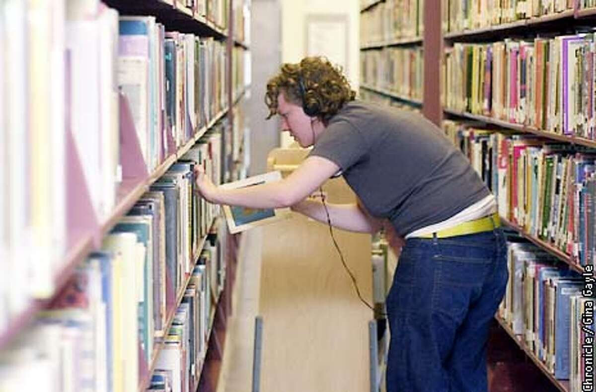 Gina Goitta shelves books in the Art and Music section in preparation for the the reopening of the refurbished Berkeley Main Library. Photo by Gina Gayle/The SF Chronicle.