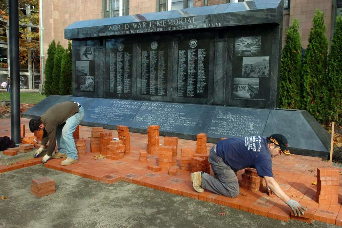Brothers Alket Meco and Arben Meco work to lay paving bricks near the new World War II Memorial, next to McLevy Hall, in downtown Bridgeport on Nov. 2nd, 2009. The area around the memorial, which was dedicated earlier this year, is being reconfigured in preperation for Veterans Day next week.
