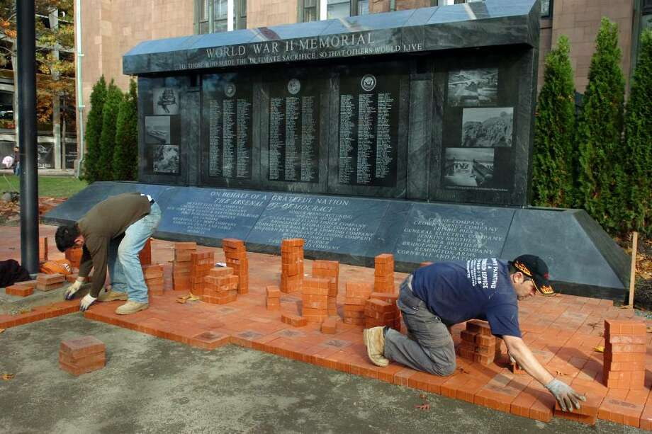 Brothers Alket Meco and Arben Meco work to lay paving bricks near the new World War II Memorial, next to McLevy Hall, in downtown Bridgeport on Nov. 2nd, 2009. The area around the memorial, which was dedicated earlier this year, is being reconfigured in preperation for Veterans Day next week. Photo: Ned Gerard / Connecticut Post