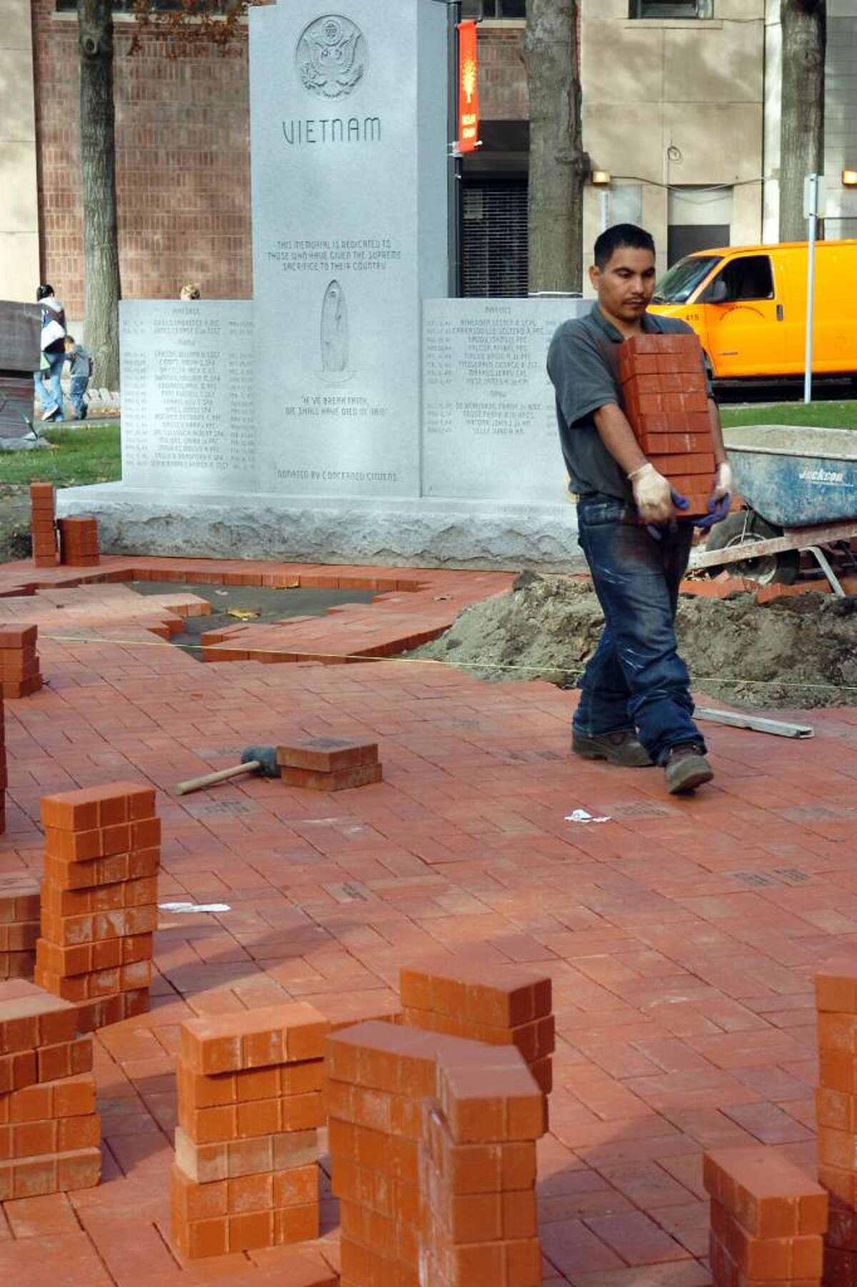 Drian (cq) Cjona carries a pile of bricks near the Vietnam Memorial, next to McLevy Hall, in downtown Bridgeport on Nov. 2nd, 2009. The Vietnam Memorial, which has stood for years, has been moved to a new location next to the recently dedicated World War II memorial.