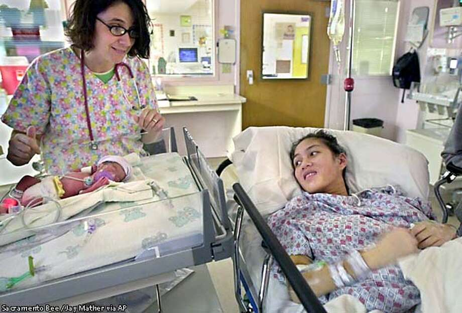 Ornsee Khamsa, right, views one of her four babies for the first time in the Neo-natal Intensive Care nursery at Sutter Memorial Hospital, in Sacramento, Calif., Monday, March 25, 2002, as nurse Lillian Daughenbaugh looks on. Khamsa and Verek Muy welcomed four identical quadruplet girls into their family, just after midnight on Monday. Identical quadruplets happen every 1-in-11 million births. (AP Photo/Sacramento Bee, Jay Mather) Photo: JAY MATHER
