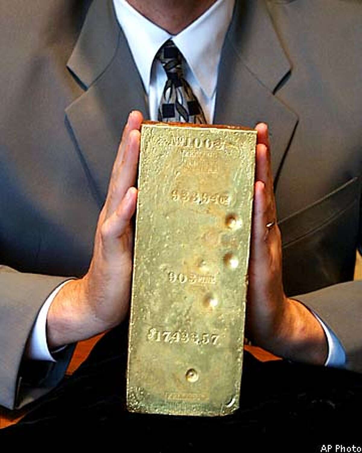 FILE--Adam Crum, vice-president of numismatics for Monaco Financial, holds an historic gold bar WEIGHING NEARLY 80 POUND TROY,, in this undated handout photo. The bar, nicknamed
