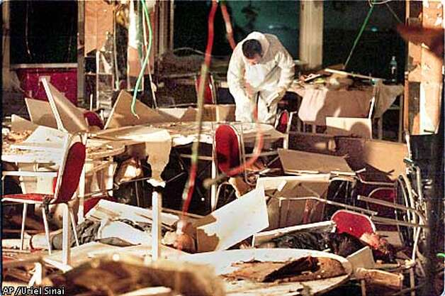 The body of a man, foreground, victim of a bomb blast, and an investigator are seen amidst the debris in the dining room of a hotel in the coastal city of Netanya, north-western Israel Wednesday March 27, 2002. A suicide bomber blew himself up Wednesday in a hotel dining room in this Israeli resort as guests gathered for a passover Seder, the ritual meal ushering in the Jewish holiday. (AP Photo/Uriel Sinai) ***ISRAEL OUT*** MAGAZINES OUT Photo: URIEL SINAI
