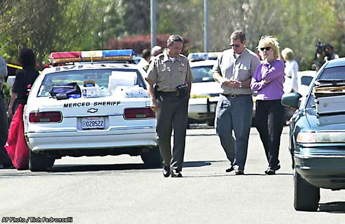 Merced County Sheriff-elect Mark Pazin, left, talks with Tom Willis, center, outside the the home were Willis' three children were slain by his ex-wife's estranged husband, in Merced, Calif., Tuesday, Marh 26, 2002. John Hogan, 49, a retired Santa Clara Sheriff's deputy, allegedly entered the home after his estranged wife, Christine McFadden, went out for a walk. According to authorities, Hogan then killed his 5-year-old daughter and three step-children before killing himself. No motive has been given for the slayings. (AP Photo / Rich Pedroncelli)