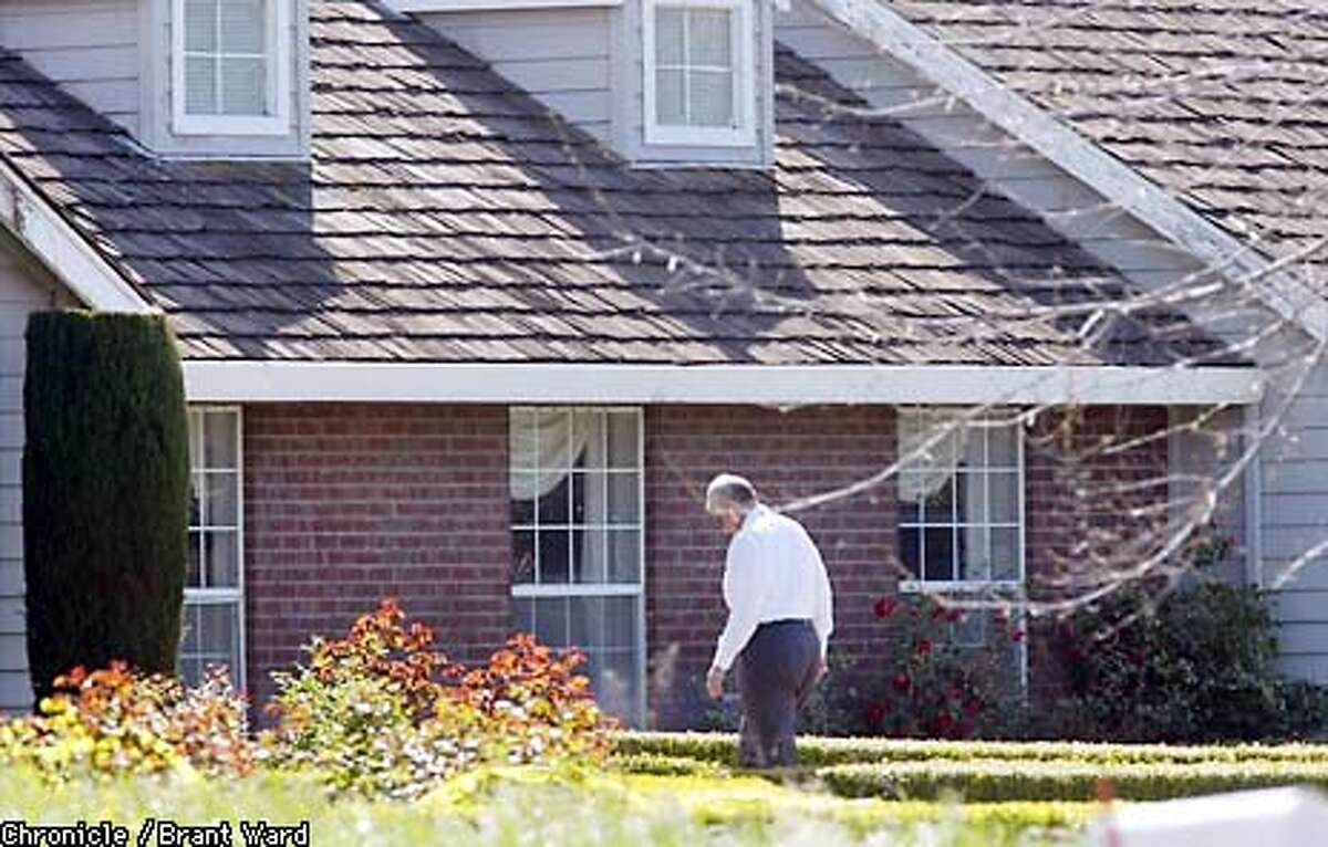 A coroners official with Merced County made his way to the front door of the Lecco Way address in Merced where five people were found dead Tuesday. By Brant Ward/Chronicle