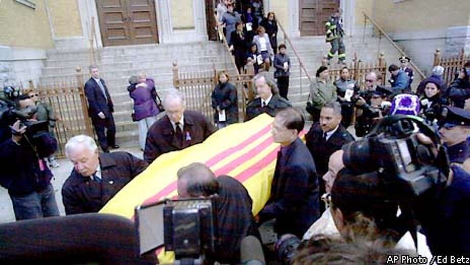 The casket containing the remains of Kathy T. Nguyen is taken from St. John Chrysostom Roman Catholic Church in the Bronx borough of New York, Monday, Nov. 5, 2001, after her funeral mass. Nguyen, an employee of the Manhattan Eye, Ear and Throat Hospital, died Wednesday of the inhaled form of anthrax. (AP Photo/Ed Betz) Photo: ED BETZ