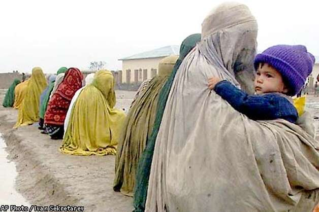 Afghan women shrouded in burqa beg near a mosque in the village of Khwaja-Bahauddin, a northern alliance stronghold, in Takhar province, northern Afghanistan, Friday, Nov.2, 2001. (AP Photo/Ivan Sekretarev) Photo: IVAN SEKRETAREV