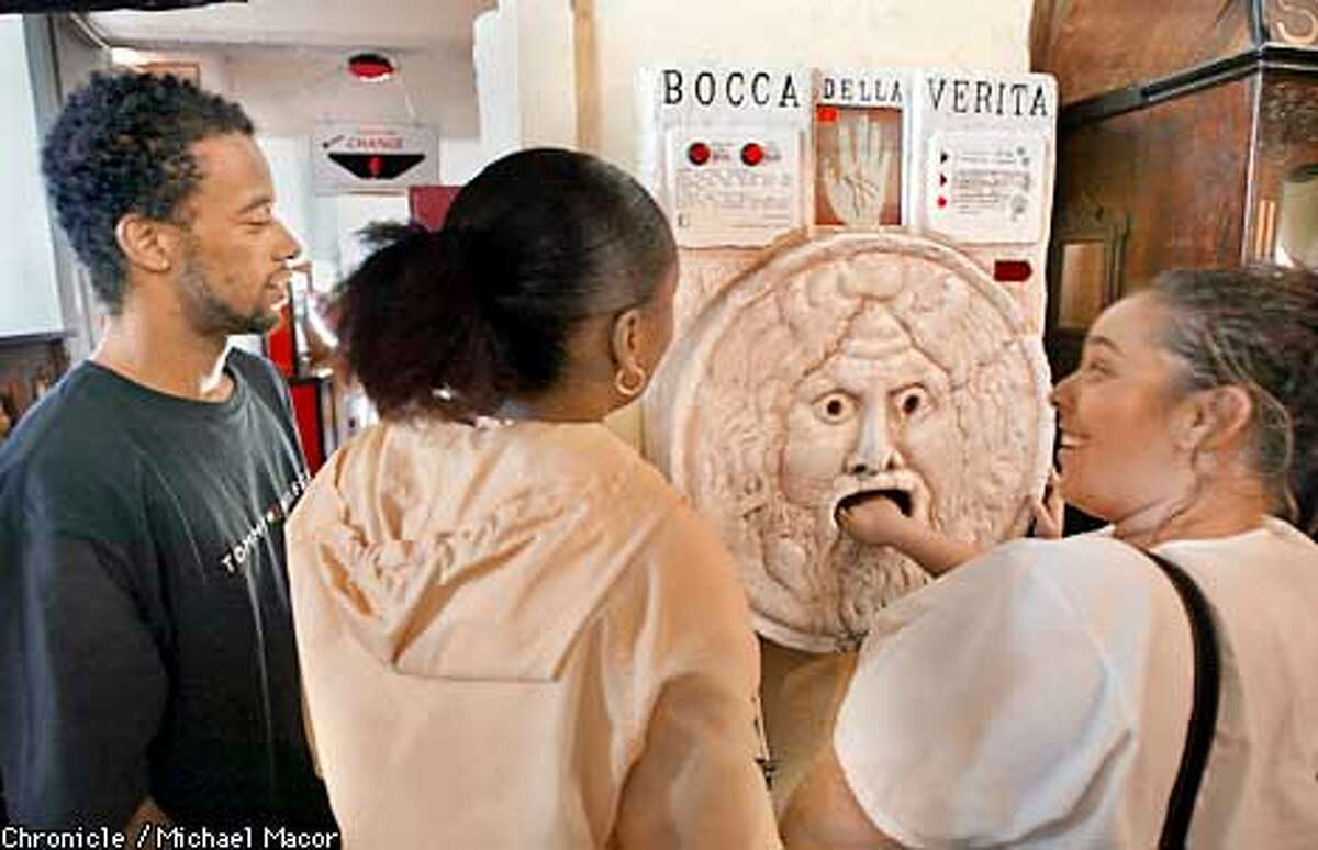 """Have your palm read for a quarter. Al and Latisha Norman watch as Chevonne Clemons has her palm read by the """"Bocca Della Verita"""" (mouth of truth). Visitors to the """"Musee Mechanic"""" below the Cliff House in San Francisco, are greeted with a sign announcing their closure coming this September. Owners have six months to find a new home. by Michael Macor/The Chronicle"""