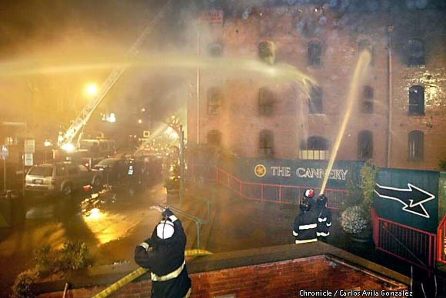 San Francisco firefighters battle a blaze at The Cannery, a historical landmark on San Francisco's Fisherman's Wharf, Sunday March 17, 2002. The fourth floor and roof of the building were completely destroyed, although the brick facade still stands, Capt. Pete Howes said. The building was built around 1907 and was undergoing renovations. (AP Photo/San Francisco Chronicle, Carlos Avila Gonzalez) Photo: CARLOS AVILA GONZALEZ