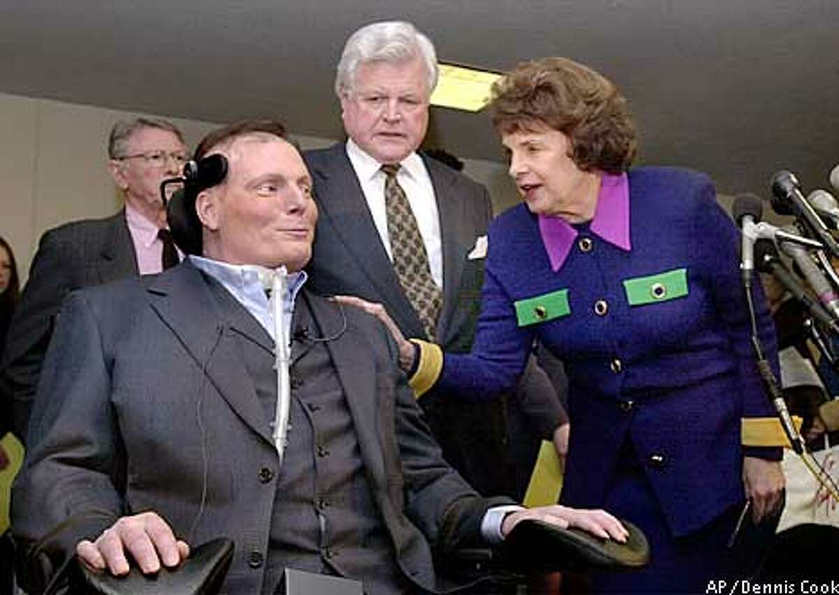 Actor Christopher Reeve, left, appears on Capitol Hill Tuesday, March 5, 2002, with Sen. Edward Kennedy, D-Mass., and Sen. Dianne Feinstein, D-Calif., to discuss the research potential of therapeutic cloning. (AP Photo/Dennis Cook)
