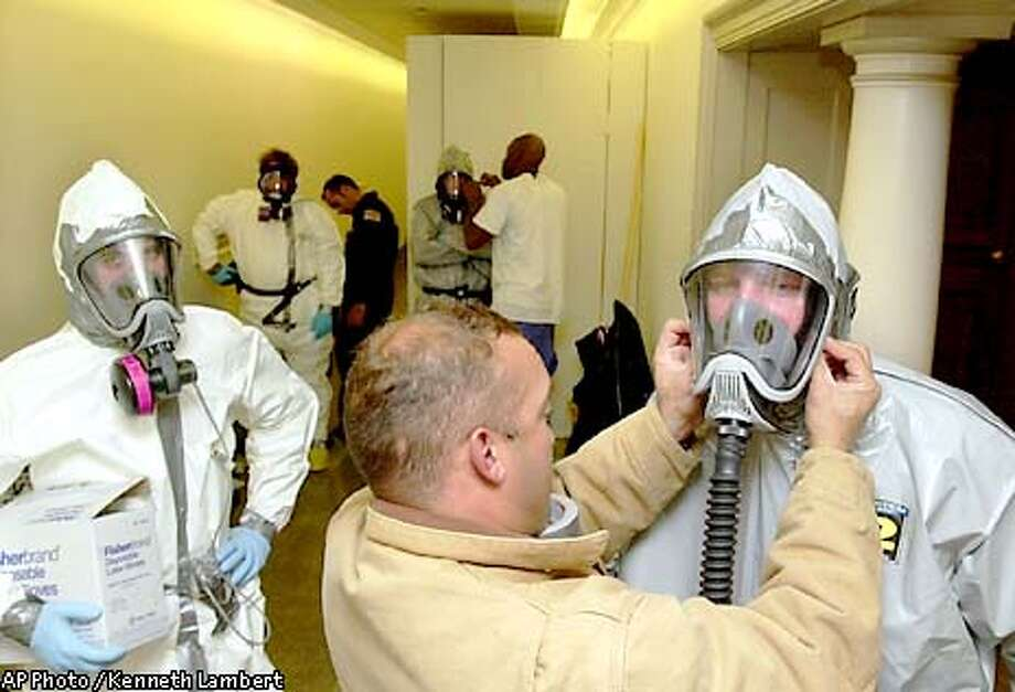 On Capitol Hill, Angelo Gonzalez, center, helps a worker with his biohazard suit, as a group prepares to enter the office of Rep. Rush Holt, D-N.J., which has been prepared with a makeshift doored entryway, background, in the Longworth House office building Monday night, Nov. 5, 2001, in Washington. Longworth opened for business today, but several offices are still sealed because of anthrax and are being prepared for decontamination. Earlier testing showed that Holt's office was contaminated with anthrax. (AP Photo/Kenneth Lambert) Photo: KENNETH LAMBERT