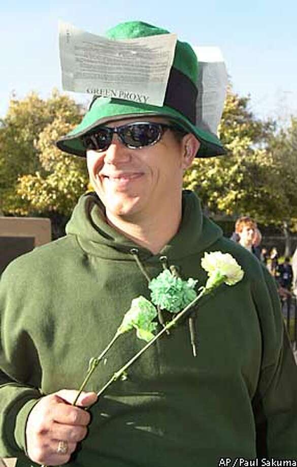 Hewlett Packard Company shareholder Lyle Ohm, of Livermore, Calif., smiles as he wears a Green Proxy card and passes out green flowers to HP shareholders before the meeting in Cupertino, Calif., Tuesday, March 19, 2002. The proxy fight over the $21 billion acquisition of Compaq Computer Corp. by HP gave individual investors a rare chance to directly influence the fate of two companies. HP's shareholder vote on the deal Tuesday. The Green Proxy was against the merger. (AP Photo/Paul Sakuma) Photo: PAUL SAKUMA