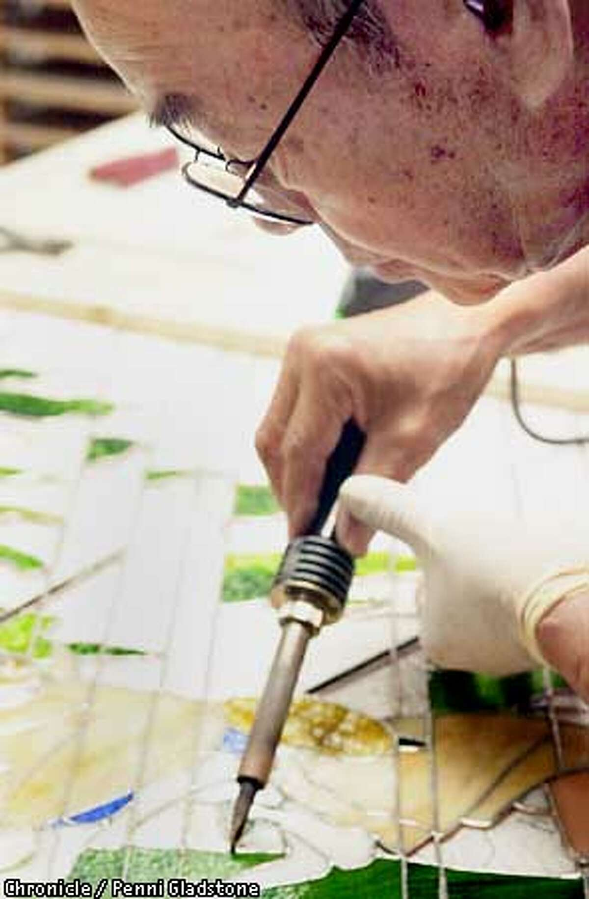 """Aanraku, stained glass studio in San Mateo. Profiled is """"Grandpa,'' Yoshinori Yakao a 79-year-old Japanese cook and swordsman,who started taking classes three years ago and now has a national reputation. Soldering a project CHRONICLE PHOTO BY PENNI GLADSTONE"""