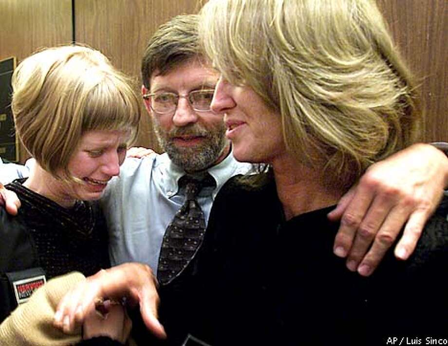 Former Symbionese Liberation Army fugitive Sara Jane Olson, right, shares an emotional moment with her daughter, Sophie Peterson, and husband, Dr. Fred Peterson, Wednesday, Oct. 31, 2001, in Los Angeles. Olson pleaded guilty Wednesday to possessing bombs with intent to murder police officers in 1975. The surprise plea came in an agreement which does not guarantee Olson a specific sentence. Her lawyers said they expected her to get about five years in prison, but the judge warned she could be sentenced to life behind bars. (AP Photo/Los Angeles Times, Luis Sinco) Photo: LUIS SINCO