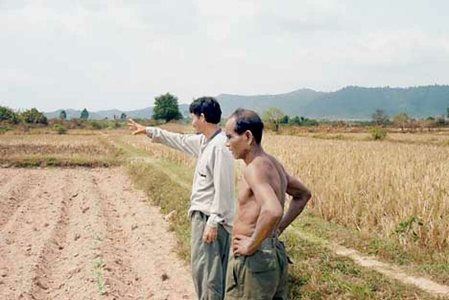 Binika San, BCC project manager, advised Khmer Rouge defector Prap Chahem about his pumpkin patch. Photo by Ben Schnayerson, special to the Chronicle