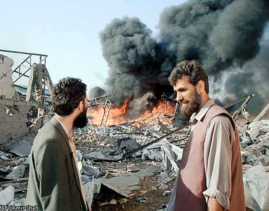 Red Cross worker Abdul Rashid, right, talks with an unidentified man as flames and plumes of black smoke billow skyward from a Red Cross warehouse, in Kabul, Afghanistan Friday Oct. 26. 2001. U.S.-led military strikes in Kabul continued Friday, hitting a Red Cross compound for a second time this month.(AP Photo/Amir Shah) Photo: AMIR SHAH