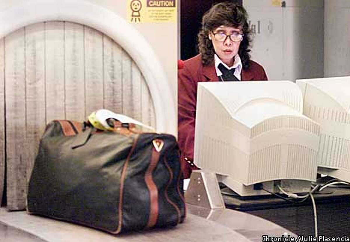 Erlinda Valencia, a San Francisco Airport security employee for over a decade, watches carefully at the contents of the luggage that are scanned by CTX security machine. (JULIE PLASENCIA/SAN FRANCISCO CHRONICLE)
