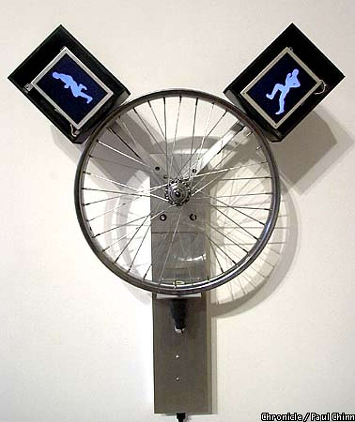 Among the sculptures displayed at the Haines Gallery is Alan Rath's spinning bicycle wheel withtwo video screens showing a human running in place. PAUL CHINN/S.F. CHRONICLE
