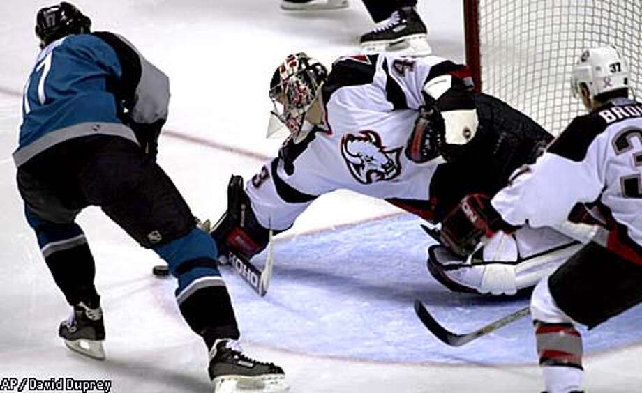 Buffalo Sabres goalie Martin Biron makes a save on a shot by San Jose Sharks left wing Scott Thornton (17) with Sabres' Curtis Brown (37) defending during the first period of the game at HSBC arena in Buffalo, N.Y., Tuesday, Oct. 23, 2001. (AP Photo/David Duprey) Photo: DAVID DUPREY