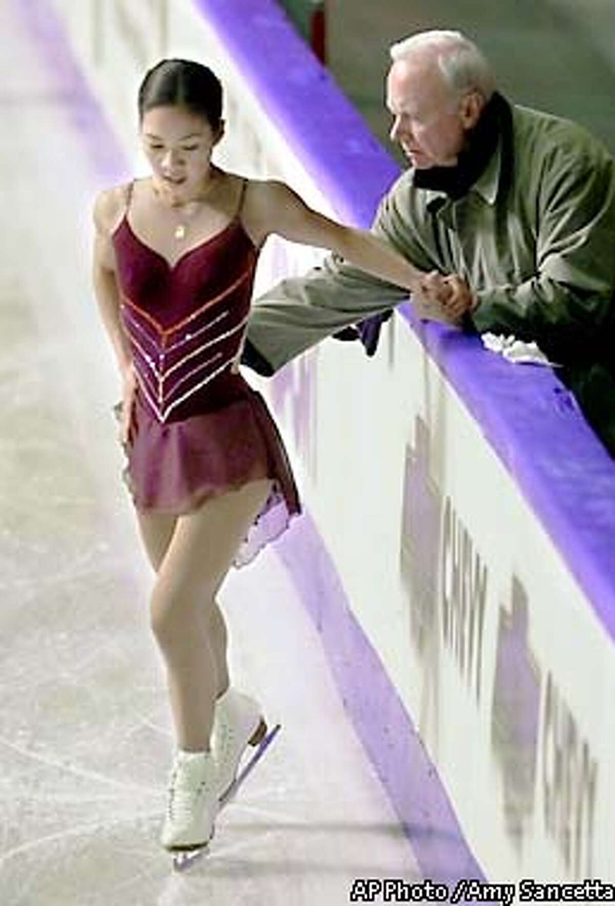 FILE--Three-time world champion Michelle Kwan, of the U.S., works with her coach Frank Carroll during a practice session for her upcoming appearance in the World Figure Skating Championships in Vancouver, Canada on Monday, March 19, 2001. Less than four months before the Salt Lake City Olympics, Michelle Kwan is taking the biggest gamble of her career. Kwan, the reigning world champion and a favorite to win gold in Salt Lake, announced Tuesday that she's split with longtime coach Frank Carroll. She plans to coach herself for now, though she didn't rule out working with someone in the future. (AP Photo / Amy Sancetta)