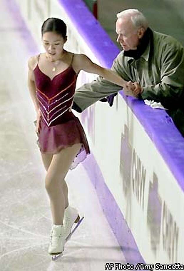 FILE--Three-time world champion Michelle Kwan, of the U.S., works with her coach Frank Carroll during a practice session for her upcoming appearance in the World Figure Skating Championships in Vancouver, Canada on Monday, March 19, 2001. Less than four months before the Salt Lake City Olympics, Michelle Kwan is taking the biggest gamble of her career. Kwan, the reigning world champion and a favorite to win gold in Salt Lake, announced Tuesday that she's split with longtime coach Frank Carroll. She plans to coach herself for now, though she didn't rule out working with someone in the future. (AP Photo / Amy Sancetta) Photo: AMY SANCETTA