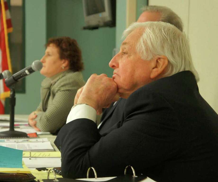 Superintendent of Schools Elliott Landon. foreground, listens to criticism of his proposed program cuts in his 2012-13 spending plan at Monday night's Board of Education meeting. Also pictured are board members Elaine Whitney and Chairman Donald O'Day, behind Landon. Photo: Paul Schott / Westport News