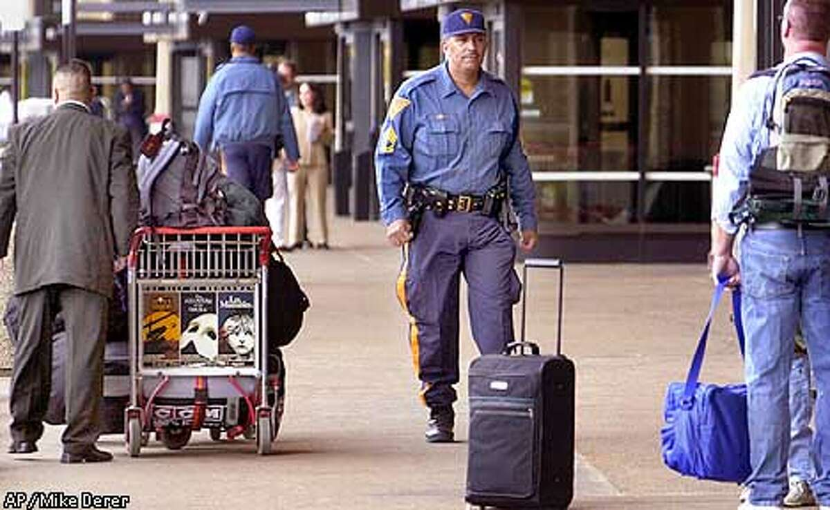 A New Jersey state trooper walks along the arrival area outside Newark International Airport in Newark, N.J., Monday, Oct. 1, 2001. Heightened security is evident at the airport, although airplane passengers have not returned to levels seen before the terrorist hijackings of Sept. 11. (AP Photo/Mike Derer)