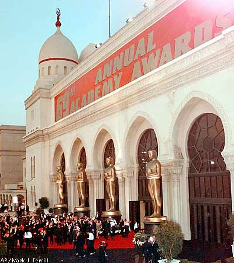 FILE--People enter the the Shrine Auditorium at the 69th Annual Academy Awards, March 24, 1997, in Los Angeles. For the last 10 years the Oscars have been hopping between the Shrine Auditorium and the Music Center's Dorothy Chandler Pavilion, but that all may come to an end if a state-of-the art theater is built in Hollywood. (AP Photo/Mark J. Terrill) Photo: MARK J. TERRILL