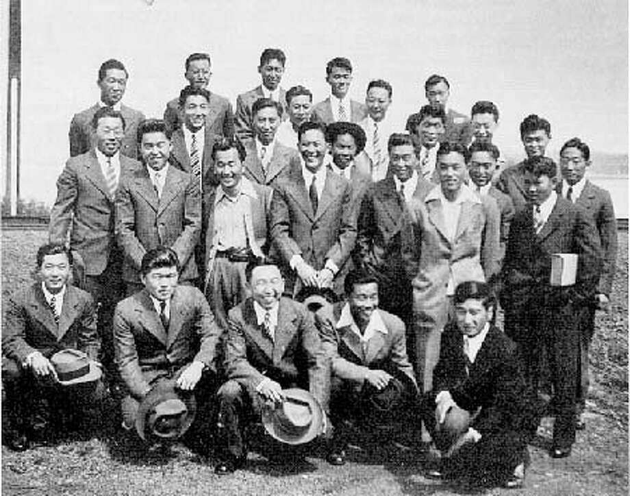Heart Mountain resisters pose in prison-issued suits on July 14, 1946, the day of their release from McNeil Island. Yosh Kuromiya stands in the back row, second fromthe left. Photo Courtesy Yosh Kuromiya.