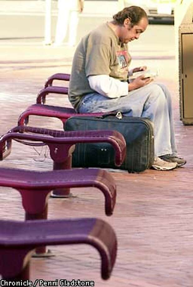 Sitting on a backless seat, drifter Jose Careaga from El Paso TX with suitcase at his side, reads a Louie Lamoure book in Hallidie plaza.  PHOTOGRAPHY BY PENNI GLADSTONE Photo: PENNI GLADSTONE