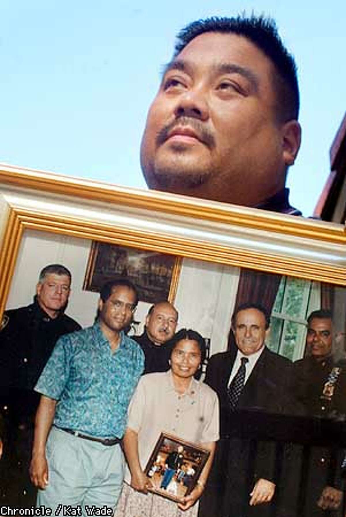 Rudy Guzman' whose brother, Randy a Martine Corps captain died in the Oaklahoma City bombing six years ago, poses with a 1996 photo of (L to R) Michael Curtin, NYPD, Fred Morgan, Manny Hernandez NYPD, Linda Morgan (holding a photo of her son Randy Guzman) NY Mayor, Rudy Guiliani, and J.R. Garcia, NYPD. Curtin who found Randy's body is now presumed dead during rescue efforts in the September 11th colapse of the WTC. SAN FRANCISCO CHRONICLE PHOTO BY KAT WADE