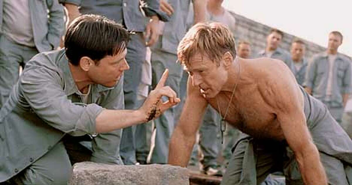 Doc (FRANK MILITARY, left) checks on the condition of Irwin (ROBERT REDFORD) during a grueling punishment in DreamWorks Pictures� THE LAST CASTLE.Photo: Elliott Marks