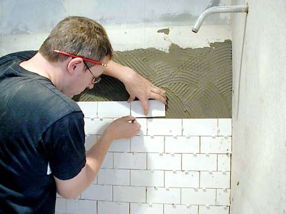 tiling_greg.jpg: Portrait of the designer as a tileman. Learning by doing, Greg Klosowski tiles his bathroom wall. (HANDOUT PHOTO) Photo: HANDOUT