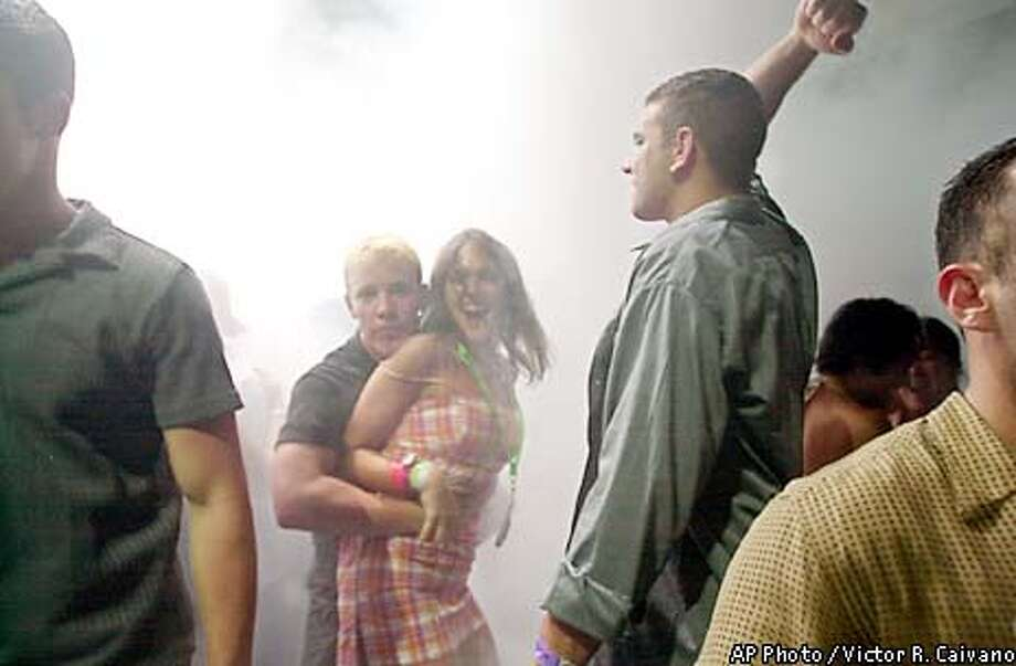 Surrounded by mist, U.S. spring breakers dance at a disco in the Caribbean resort city of Cancun, Mexico, on Thursday, March 7, 2002. Thousands of college and high school students visit Cancun each year during the six-week Spring Break period. (AP Photo/Victor R. Caivano) Photo: VICTOR R. CAIVANO