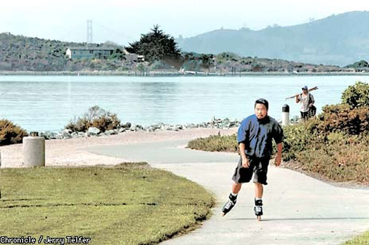 An inline skater cruises along Marina Bay development Esplanade in Richmond, CA. The Golden Gate Bridge is in the distance. CHRONICLE STAFF PHOTO BY JERRY TELFER