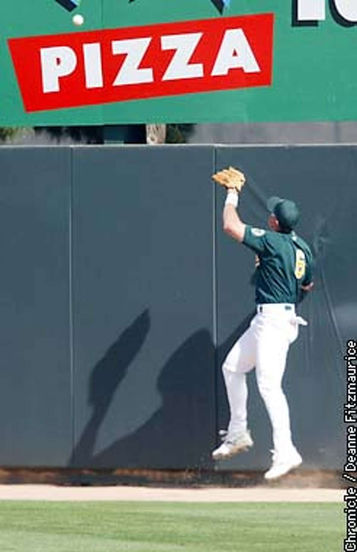 """Geoff Jenkins' 2 run homer dotted the """"i"""" in pizza on this sign as rightfielder Adam Piatt tried in vain to save it. Oakland A's vs Milwaukee Brewers at spring training in Phoenix, Arizona. CHRONICLE PHOTO BY DEANNE FITZMAURICE"""