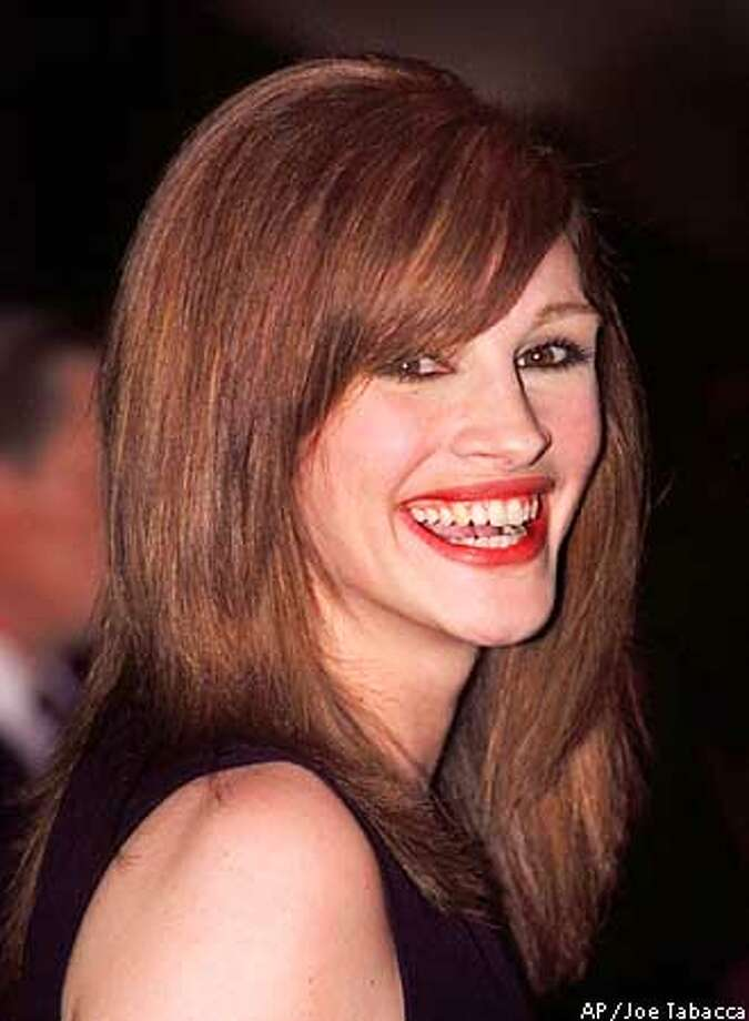 Julia Roberts , shown in this July, 1995 file photo, was photographed dancing on a bar at the night spot Hogs & Heifers in New York City early Sunday, Sept. 8, 1996. Roberts also slipped her bra out one arm of her top and left it behind as a souvenir, as have Ashley Judd, Darryl Hannah and Drew Barrymore, the New York Daily News reported. ``I was just having fun inside,'' Roberts said as she left. (AP Photo/Joe Tabacca) ALSO RAN: 4/1/99