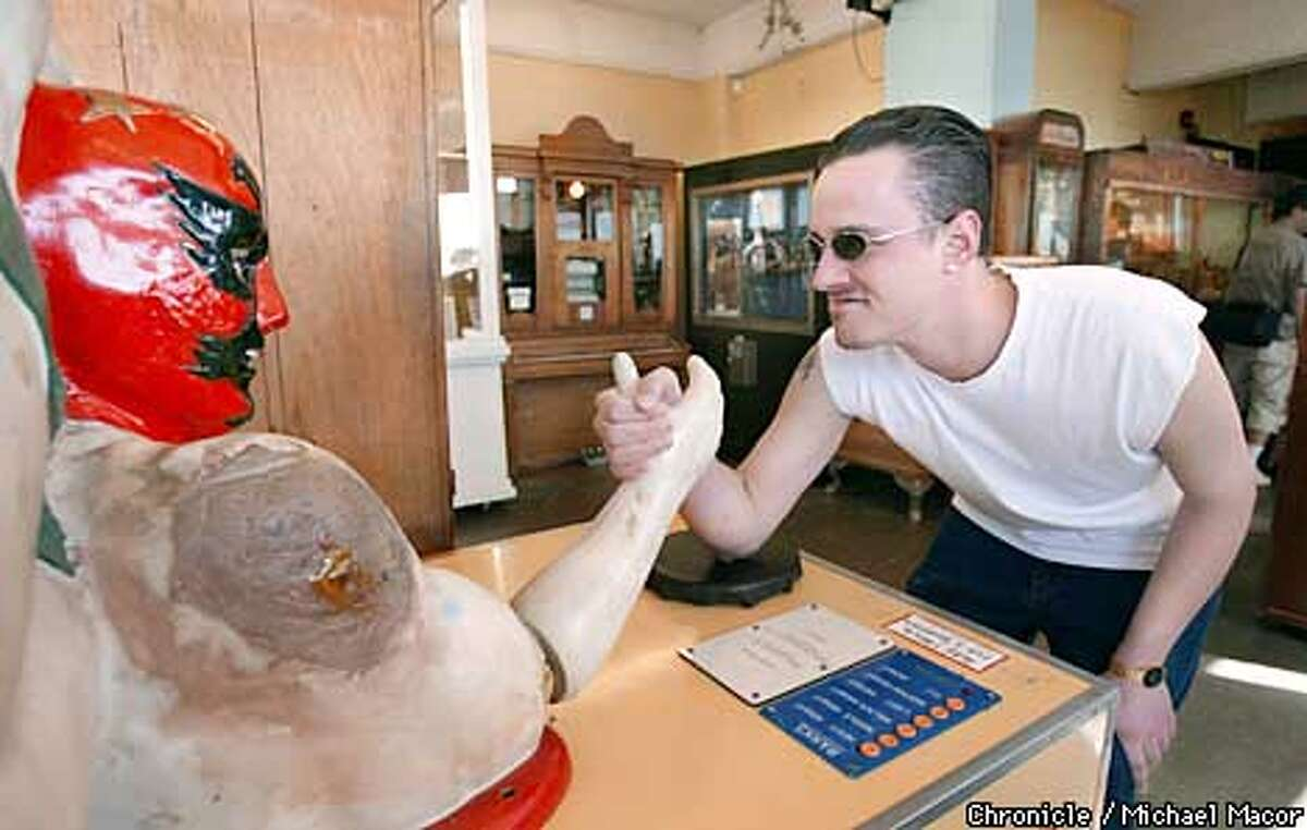 """David Peerman of SF gets ready for an arm wrestling contest against a mechanical opponet. Visitors to the """"Musee Mechanic"""" below the Cliff House in San Francisco, are greeted with a sign announcing their closure coming this September. Owners have six months to find a new home. by Michael Macor/The Chronicle"""