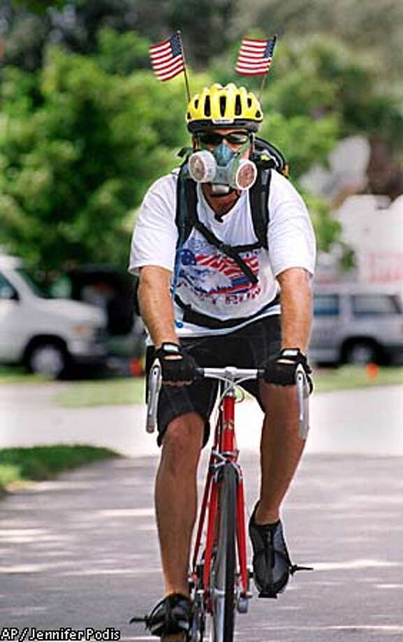 An unidentified bicyclist sporting U.S. flags on his helment and a respirator rides in front of the American Media Inc. building, where an ongoing investigation into the anthrax virus continues Wednesday, Oct. 10, 2001, in Boca Raton, Fla. (AP Photo/Palm Beach Post, Jennifer Podis) Photo: JENNIFER PODIS
