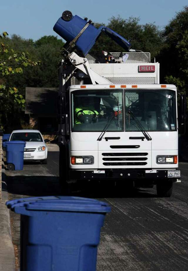 A City of San Antonio recycling truck picks up and empties a 96-gallon cart on a residential run.  JOHN DAVENPORT/jdavenport@express-news.net