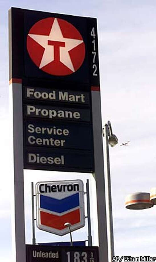 A Chevron sign is framed inside a Texaco sign at the corner of Boulder Highway and Desert Inn Road in Las Vegas, Sunday, Oct. 15, 2000. Chevron Corp. reportedly reached a deal to acquire Texaco Inc. for about $35.1 billion in stock, creating the world's fourth-largest oil company. The boards of both companies approved the transaction, The Wall Street Journal reported on Sunday, citing sources familiar with the matter. A formal announcement is expected Monday morning. (AP Photo/Las Vegas Sun, Ethan Miller) Photo: ETHAN MILLER