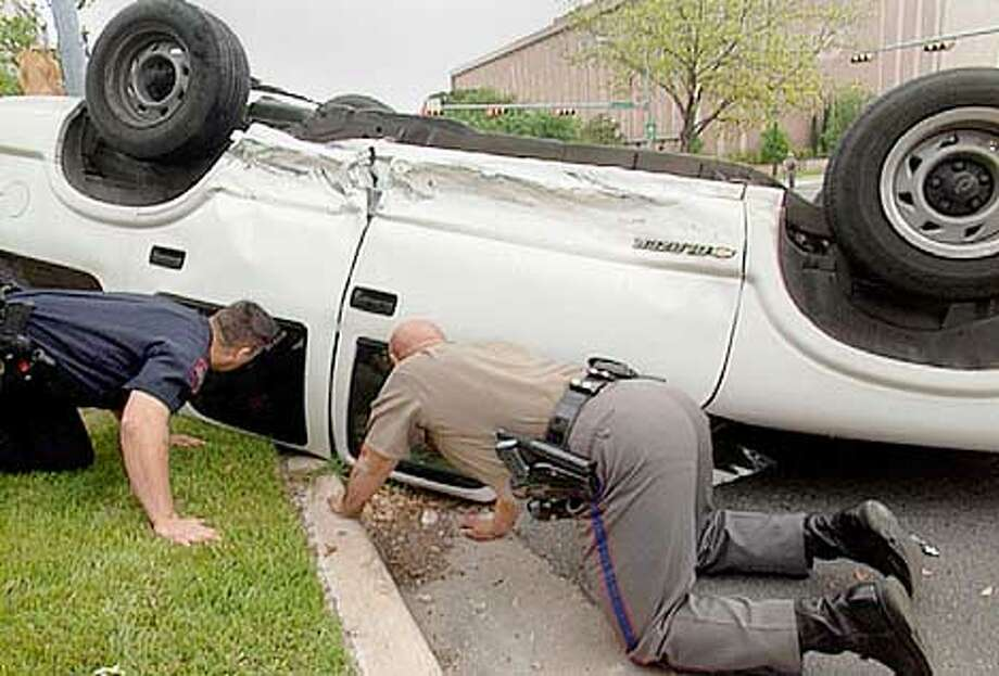 Rescue workers attempt to reach the driver of an overturned SUV in Austin, Texas. WGBH/FRONTLINE Photo: HANDOUT