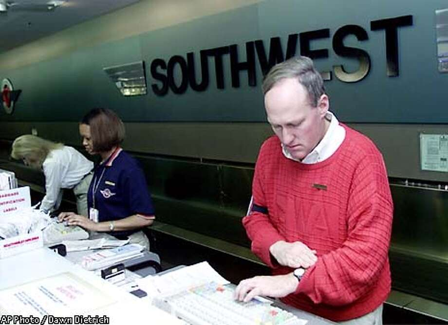 Bill Waggener, who has worked for Southwest Airlines for three years, checks his watch to make sure a passanger will make a flight on time, Monday, Feb. 18, 2002, at Love Field in Dallas. Southwest, which has 33,000 employees, says it plans to hire 250 pilots, 1,200 flight attendants and 2,600 other workers. At far left is Martha Carter and second from left is Kelli Jackson. Dallas-based Southwest is the only major U.S. airline still making money. The largest carriers, American and United, lost $3.8 billion between them last year. (AP Photo/Dawn Dietrich) Photo: DAWN DIETRICH, Associated Press