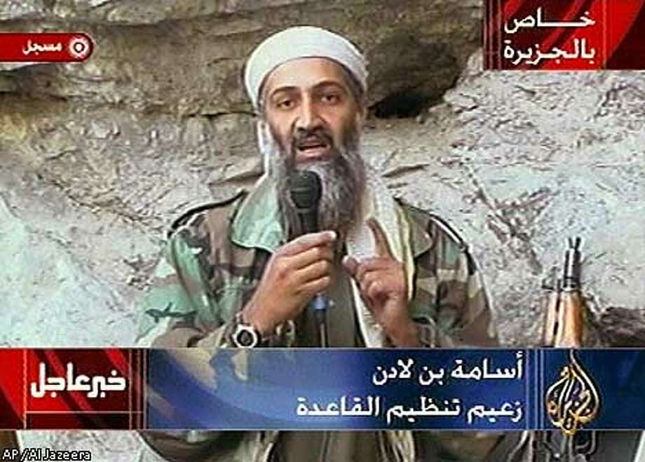 """ADDS TRANSLATION OF SUPERIMPOSED GRAPHICS--Osama bin Laden is seen at an undisclosed location in this television image broadcast Sunday Oct. 7, 2001. Bin Laden praised God for the Sept. 11 terrorist attacks and swore America """"will never dream of security"""" until """"the infidel's armies leave the land of Muhammad,"""" in a videotaped statement aired after the strike launched Sunday by the U.S. and Britain in Afghanistan. Graphic at top right reads """"Exclusive to Al-Jazeera."""" At bottom right is the station's logo which reads """"Al-Jazeera."""" At top left is """"Recorded."""" Bottom left is """"Urgent news."""" At bottom center is """"Osama bin Laden, Leader of the al-Qaida."""" (AP Photo/Al Jazeera)"""