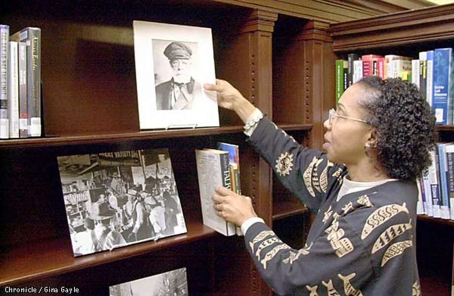 Linda Jolivet, reference librarian of the African American Museum and Library at Oakland straightends a portrait of (name coming) as she stocks shelves in the reference library. Photo by Gina Gayle/The SF Chronicle. Photo: GINA GAYLE