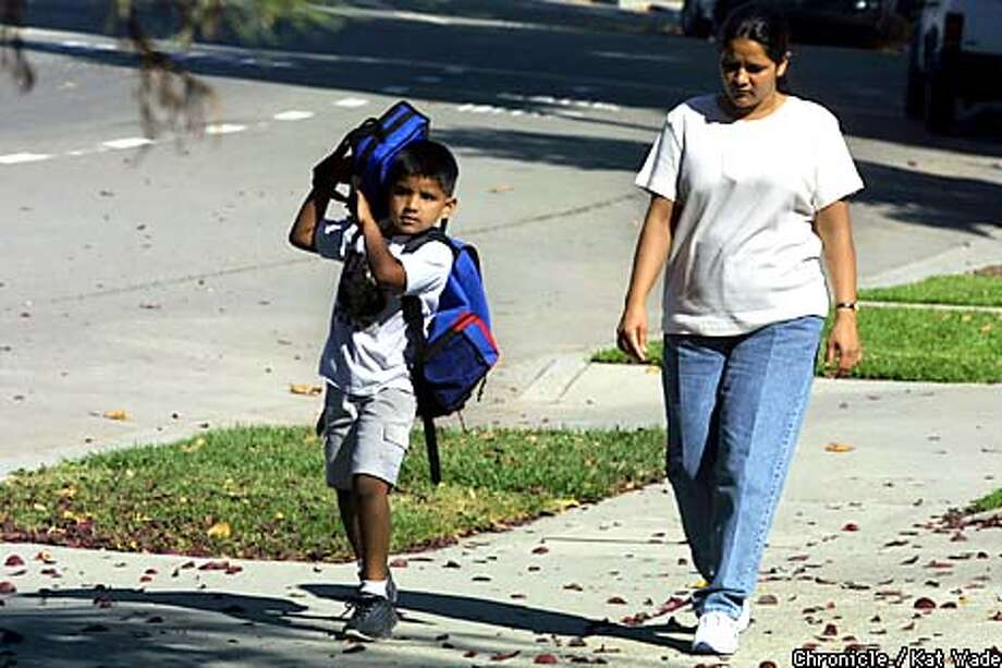 With his mother, Vandana (CQ) Srivastava at his side, First grader, Karan (CQ) Saravana (CQ), 6, gets picked up from Fairlands Elementary School in Pleasanton. SAN FRANCISCO CHRONICLE PHOTO BY KAT WADE Photo: KAT WADE