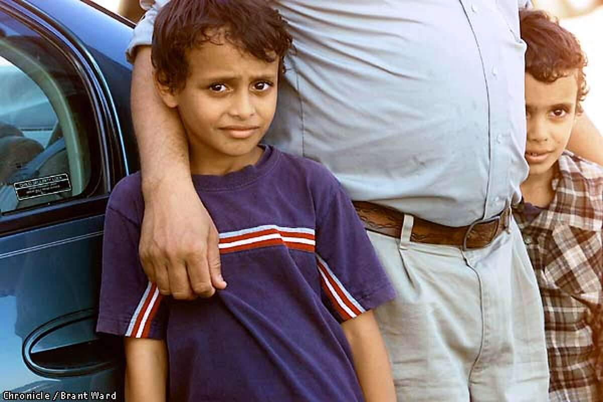 Middle Easterners from many countries live in the Reedley area. Here Abdo Saad holds his two sons during a visit to the Ahmed residence. The boys, l-r, Akram and Ibrahim, are brought to show the family sadness although the Saad family hardly knew the shooting victim. By Brant Ward/Chronicle