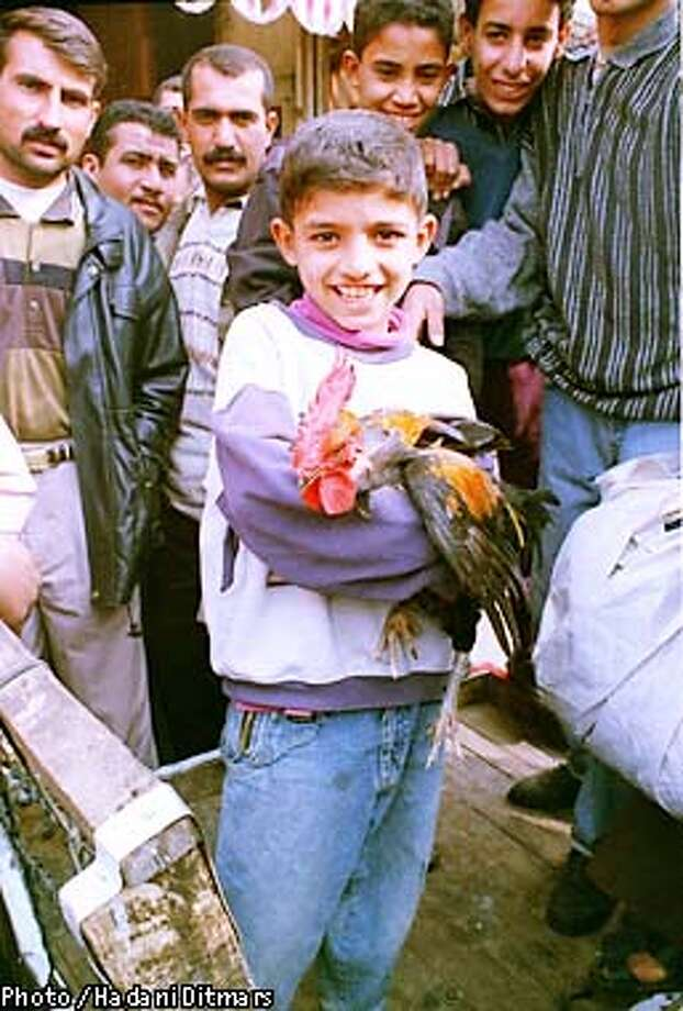 A BOY HAPPILY CLUTCHED A ROOSTER HE BOUGHT AT AN OPEN-AIR MARKET IN BAGHDAD, IRAQ.  PHOTO BY HADANI DITMARS Photo: HANDOUT