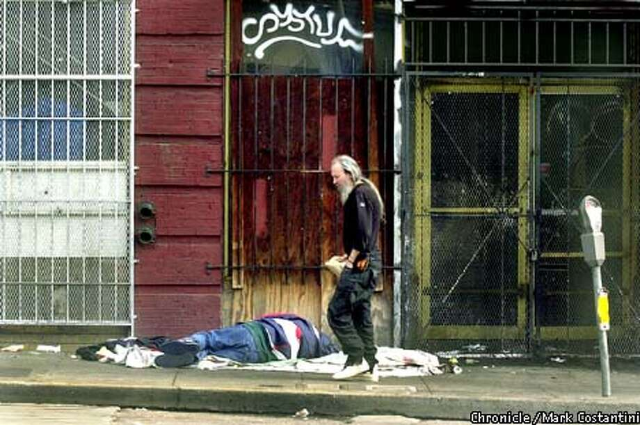 IN THE MORNING, A MAN WALKS PAST A GUY SLEEPING ON SIXTH STREET, TARGET OF FUTURE CLEAN-UP EFFORT BY MAYOR WILLIE BROWN. PHOTO: MARK COSTANTINI/THE CHRONICLE Photo: MARK COSTANTINI
